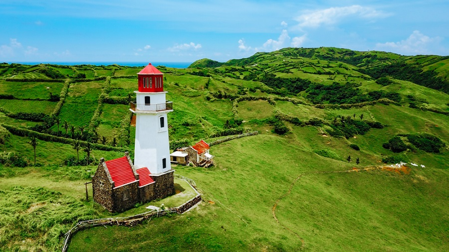 lighthouse in batanes surrounded by rolling hills