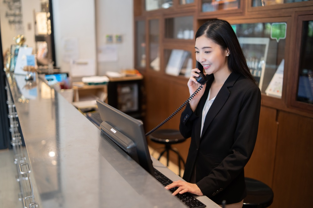 hotel receptionist answering the phone