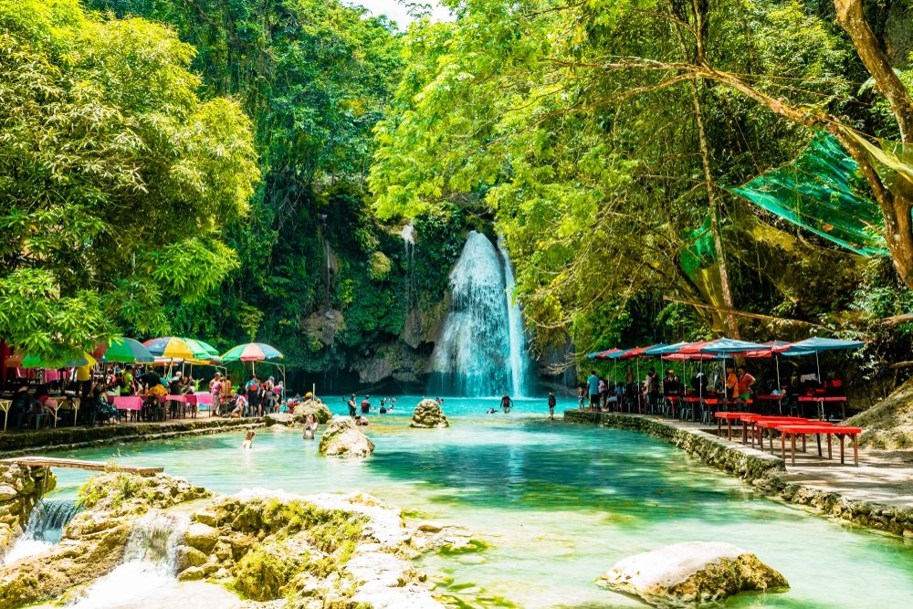 tourists and cottages in kawasan falls